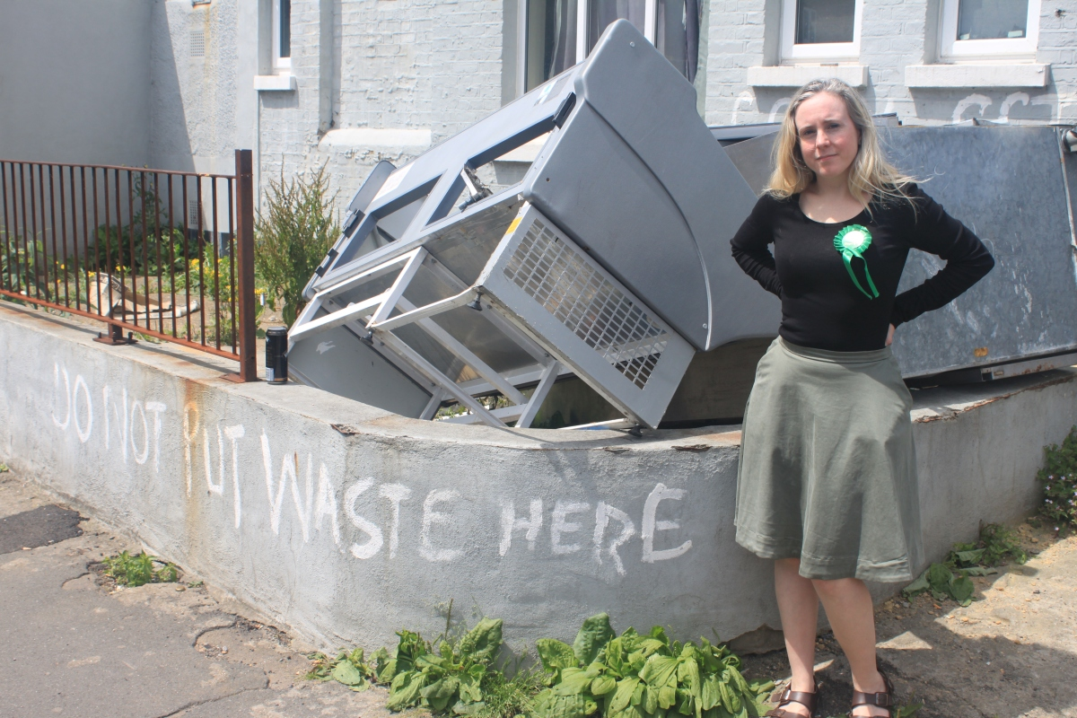 Elisabeth stands in front of dumped office furniture. The garden wall next to it has 'Do not put waste here' painted on it in big letters